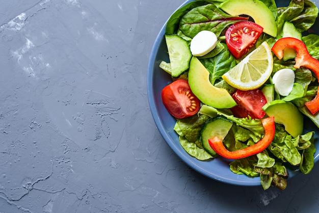 Widok z góry szary talerz z soczystymi, jasnymi warzywami, awokado, cytryną, pomidorem, papryką, ogórkiem i sałatką z mozzarelli