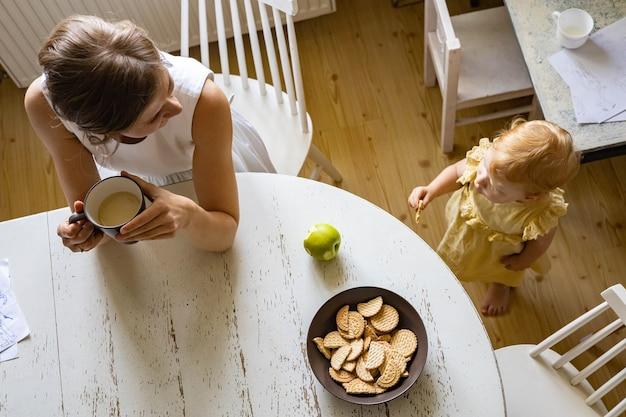 Widok z góry szczęśliwa matka i urocza mała córka pijąca herbatę w vintage kuchnia rustykalna wnętrze domu