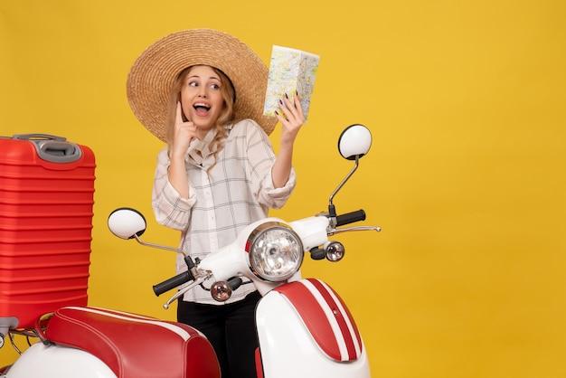 Widok z góry szczęśliwa uśmiechnięta młoda kobieta ubrana w kapelusz, zbierając swój bagaż, siedząc na motocyklu i trzymając mapę