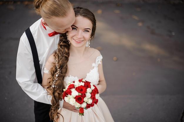 Widok z góry szczęśliwego małżeństwa z bukietem ślubnym, pozowanie na zewnątrz w ciepły dzień