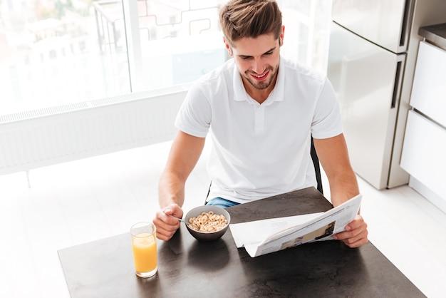 Widok z góry szczęśliwego młodego człowieka z gazetą siedzącą i jedzącym śniadanie w kuchni