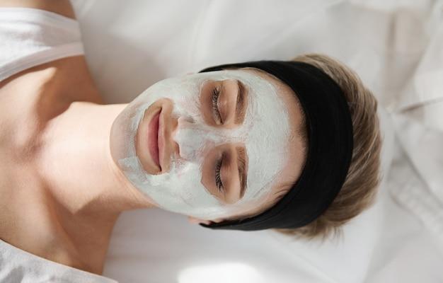 Widok z góry szczęśliwej młodej kobiety z maską kosmetyczną na twarzy relaksujący i cieszący się zabiegiem kosmetycznym w salonie spa. profesjonalna koncepcja pielęgnacji skóry w nowoczesnych salonach kosmetycznych spa