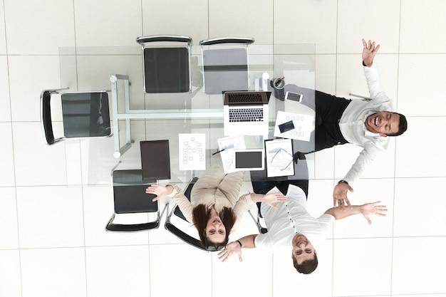Widok z góry. szczęśliwi pracownicy siedzący przy biurku. pojęcie pracy zespołowej