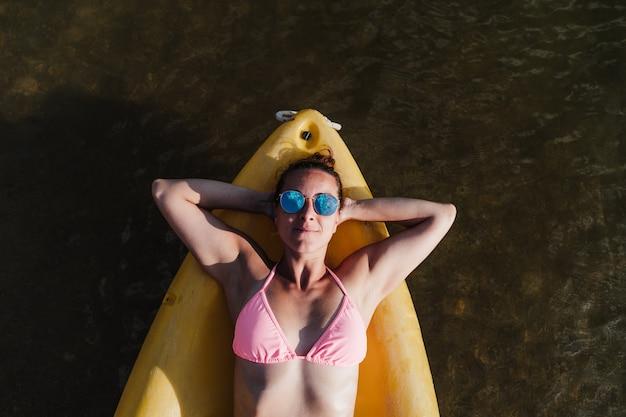 Widok z góry szczęśliwy kaukaski kobieta leżąc na żółtym kajaku w jeziorze w słoneczny dzień. czas letni. sport, przygoda i przyroda. kobieta w stroju kąpielowym i okularach przeciwsłonecznych