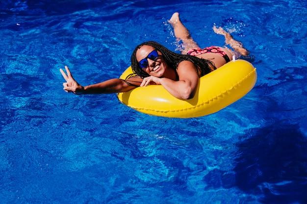 Widok z góry szczęśliwy kaukaski kobieta relaks na żółte pączki nadmuchiwane przy basenie. co znak v rękami. czas letni, wakacje i styl życia