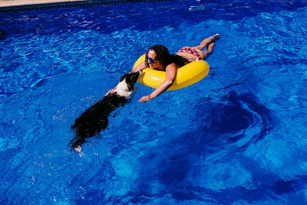 Widok z góry szczęśliwy kaukaski kobieta relaks na żółte pączki nadmuchiwane przy basenie. ładny pies rasy border collie do basenu. czas letni, wakacje i styl życia