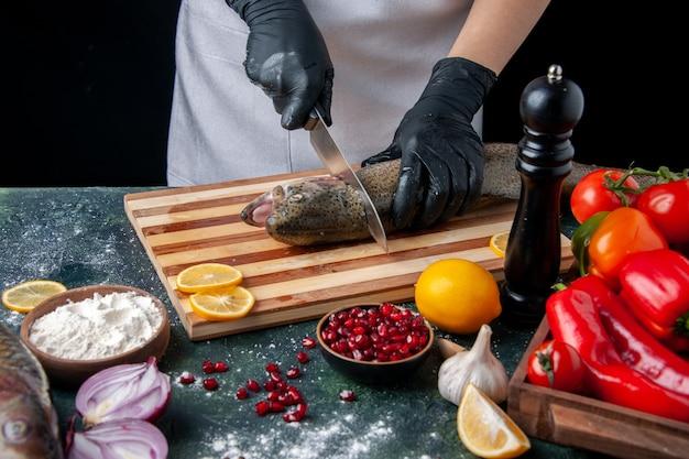 Widok z góry szef kuchni tnącej głowę ryby na desce do krojenia młynek do pieprzu miska do mąki nasiona granatu w misce warzywa na kuchennym stole