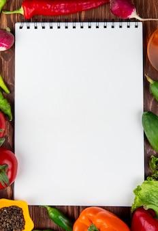 Widok z góry szkicownika i świeżych warzyw kolorowe papryki zielone papryki chili pomidory i czarne ziarna pieprzu na rustykalnym drewnie