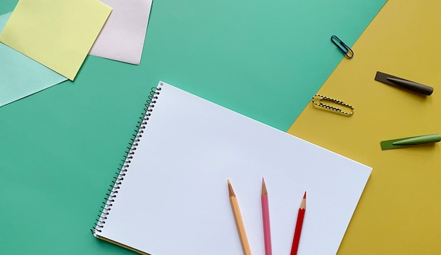 Widok z góry szkicownika z kolorowymi ołówkami spinaczami do papieru i ołówkami na zielono i żółto