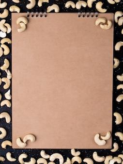 Widok z góry szkicownika z solonymi prażonymi pistacjami rozrzuconymi na czarnym tle