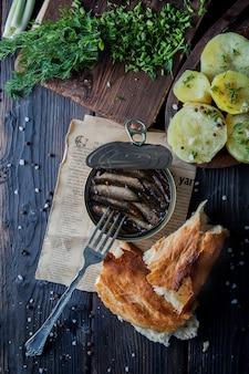 Widok z góry szprot w puszkach z gotowanymi ziemniakami oraz widelcem i chlebem