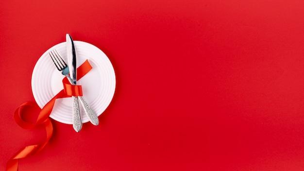 Widok z góry sztućców na talerzu ze wstążką i miejsca kopiowania