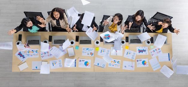 Widok z góry tabeli sześciu azjatyckich kobiet biznesu siedzących w linii prostej na drewnianym stole konferencyjnym i rzucających wykresy i wykresy w powietrze w biurze. koncepcja spotkania biznesowego.