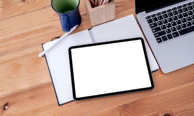Widok z góry tablet z pustym ekranem i materiały na drewnianym stole.