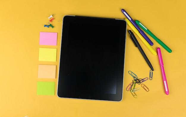 Widok z góry tabletu i przyborów szkolnych, takich jak kolorowe markery, naklejki i clipery na żółtym tle, miejsce na tekst.