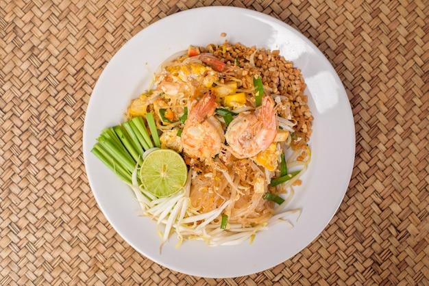 Widok z góry tajskiej tradycyjnej żywności pad thai makaron z krewetkami w naczyniu na drewnianym stole