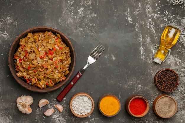 Widok z góry talerz fasolki szparagowej z apetyczną fasolką szparagową z pomidorami obok widelca czosnkowego butelka oleju miska przypraw na ciemnym stole