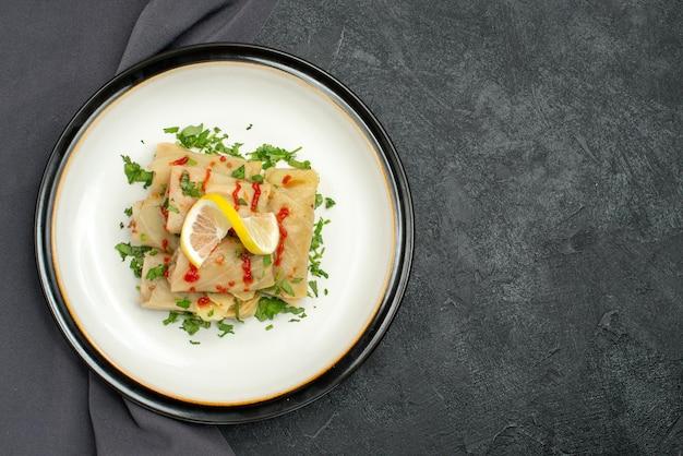 Widok z góry talerz na obrusie biały talerz gołąbki z ziołami cytryna i sos na szarym obrusie po lewej stronie ciemnego stołu