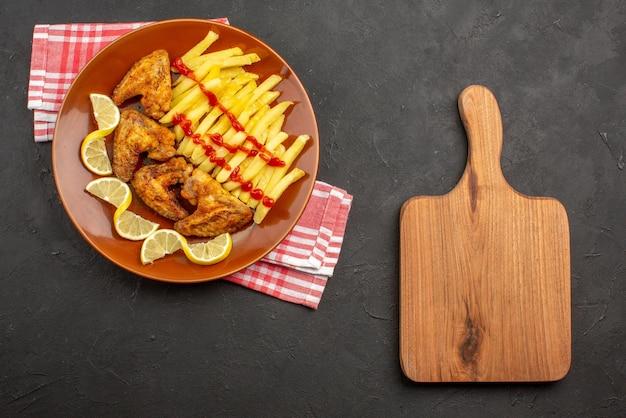 Widok z góry talerz na obrusie pomarańczowy talerz z apetycznymi frytkami skrzydełka kurczaka ketchup i cytryna na obrusie w różowo-białą kratkę obok deski do krojenia