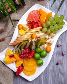Widok z góry talerz owoców pomarańczowy truskawkowy bananowy kiwi gruszka winogrona i wiśnia śliwka
