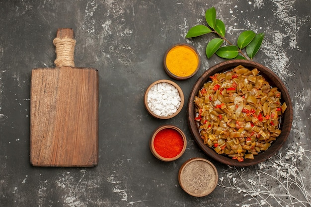 Widok z góry talerz przypraw z fasolką szparagową obok misek kolorowych liści przypraw obok drewnianej deski do krojenia i gałęzi drzew na ciemnym stole