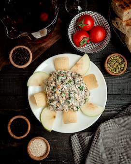 Widok z góry talerz sałatki jabłkowej z sałatą kukurydzianą, kurczakiem, majonezem i rodzynkami