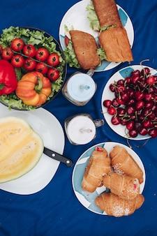 Widok z góry talerzy ze świeżymi zdrowymi warzywami, czerwonymi wiśniami, soczystym melonem, pysznymi kanapkami z kurczakiem, czekoladowymi rogalikami i napojami. koncepcja pikniku i produktów.