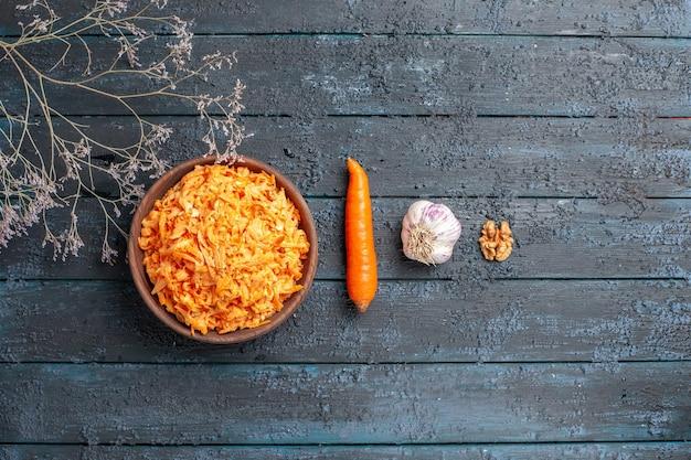 Widok z góry tartej sałatki z marchwi wewnątrz brązowego talerza na ciemnoniebieskim rustykalnym biurku sałatka zdrowotna dojrzała dieta w kolorze warzyw