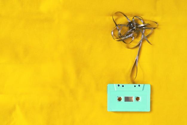 Widok z góry taśmy kasetowej na żółtym tle materiału tkaniny z splątane wstążki. efekt filtra retro i stylu vintage