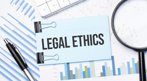 Widok z góry tekstu etyki prawnej z kalkulatorem, lupą i długopisem na wykresach finansowych