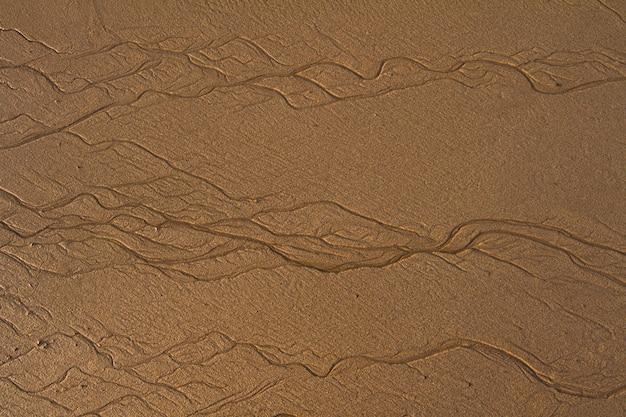 Widok z góry teksturowane linie tła na piasku na plaży utworzone przez odpływ.