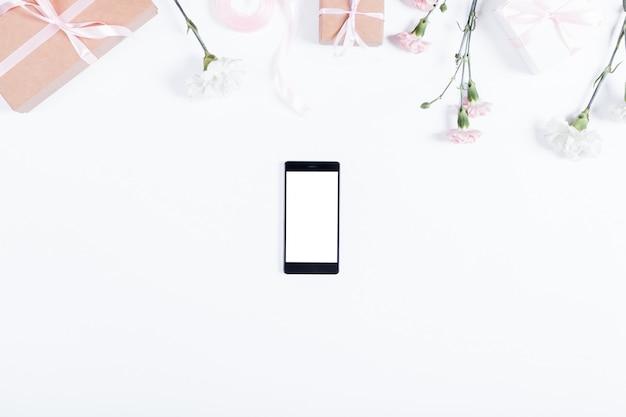 Widok z góry telefonu komórkowego i ozdoby świąteczne na białym stole