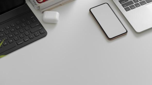 Widok z góry telefonu, tabletu, laptopa, innych materiałów biurowych i miejsca na kopię na białym stole