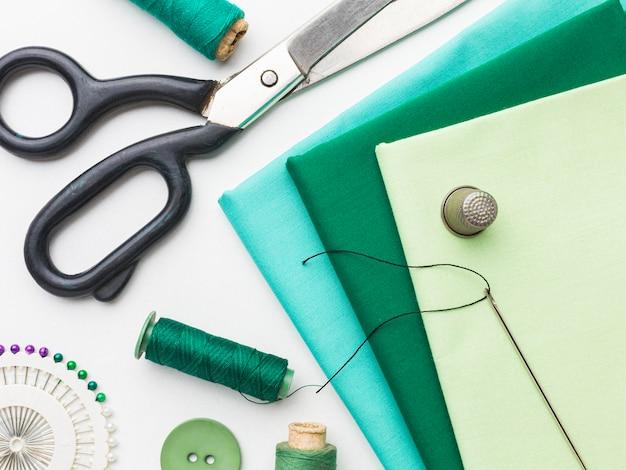 Widok z góry tkanin z naparstkiem i nożyczkami