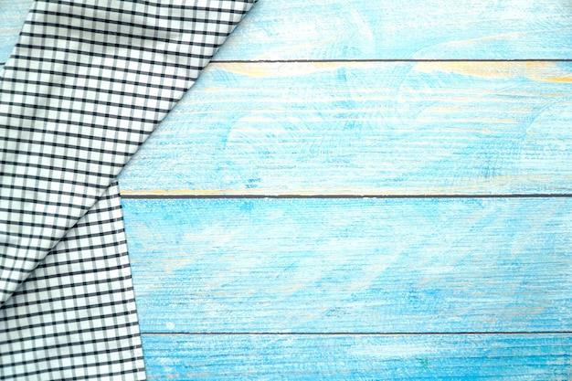 Widok z góry tkaniny w kratkę czarno-białą na niebieskim tle stołu z drewna.