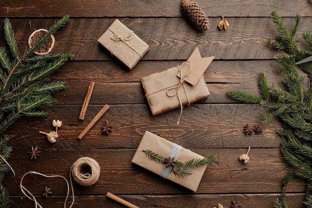 Widok z góry tło bożonarodzeniowe z prezentami rzemieślniczymi na drewnianym stole ozdobionym gałęziami jodły kopiuj...