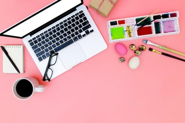Widok z góry tło laptopa i zestaw farb do przygotowania na wielkanoc na różowym tle,