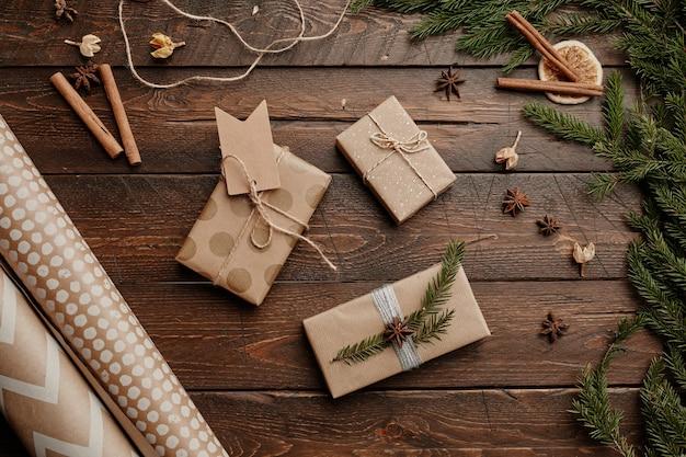 Widok z góry tło prezentów świątecznych zawinięty w papier rzemieślniczy na rustykalnej drewnianej przestrzeni kopii stołu