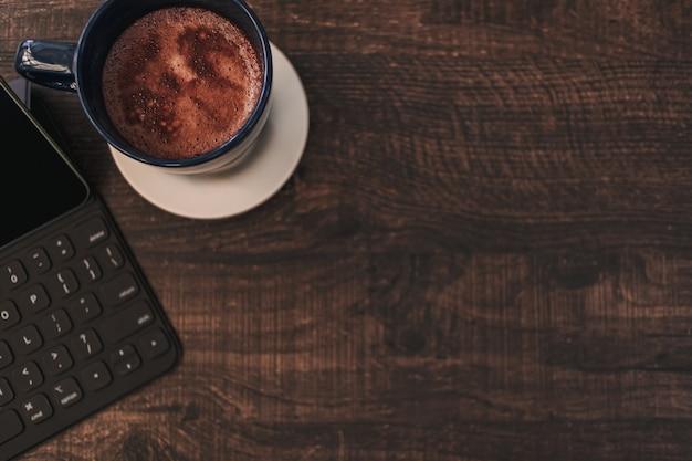 Widok z góry tło tabletu i gorącego napoju na drewnianym biurku