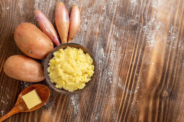 Widok z góry tłuczone ziemniaki ze świeżymi ziemniakami na drewnianym biurku składnik posiłku kolor ciasta piec