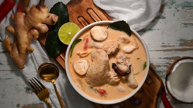 Widok z góry tom kha gai, zupa z mleka kokosowego z kurczakiem, tradycyjne tajskie jedzenie z dodatkami