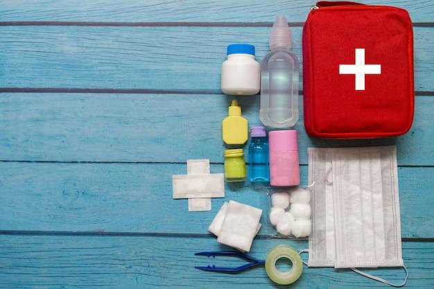 Widok z góry torba pierwszej pomocy dzieciak z zaopatrzenia medycznego na tle drewna.