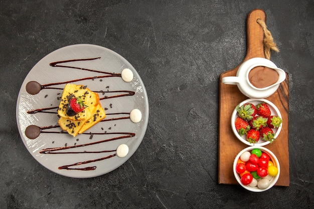Widok z góry tort z jagodami z czekoladą i truskawkami na talerzu obok deski do krojenia z miseczkami cukierków w sosie czekoladowym i truskawkami