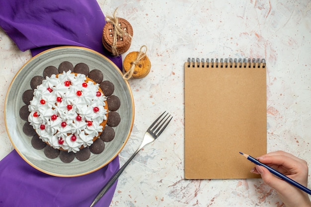 Widok z góry tort z kremem cukierniczym na owalnym talerzu fioletowe szalowe ciasteczka wiązane liną widelec notatnik ołówek w kobiecej dłoni na białym stole