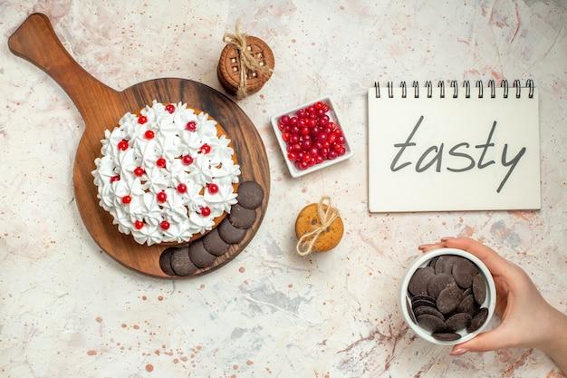 Widok z góry tort z kremem z białego ciasta na desce do krojenia miska z jagodami miska czekolady w kobiecej dłoni ciasteczka związane sznurkiem na szarym stole