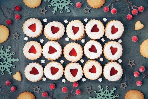 Widok z góry tradycyjnych świątecznych ciastek linzer z czerwonym dżemem na ciemności