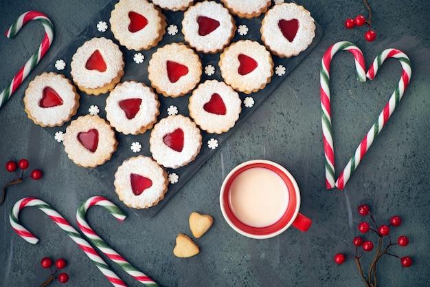 Widok z góry tradycyjnych świątecznych ciastek linzer z czerwonym dżemem na ciemnym stole ozdobionym jagodami i pędami cukierków.