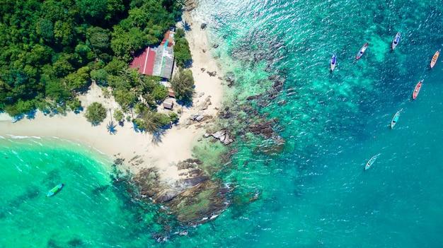 Widok z góry: tropikalna wyspa z palmami, lazurowe morze i wiele tajskich tradycyjnych łodzi obok.