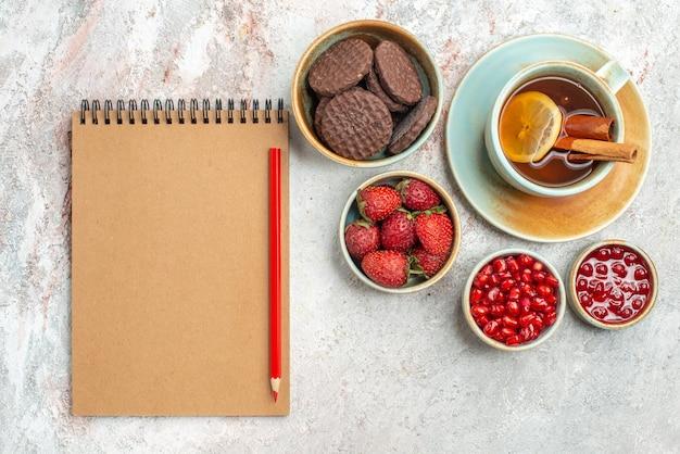 Widok z góry truskawki krem notatnik czerwony ołówek biała filiżanka czarnej herbaty z cytryną miski jagód czekoladowe ciasteczka granat na stole