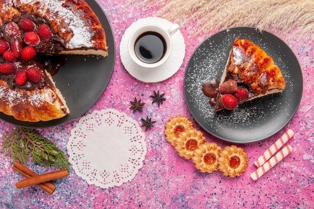 Widok z góry truskawkowy tort czekoladowy z ciasteczkami i herbatą na różowym biurku